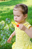 Portrait of little girl blowing soap bubbles Stock Images
