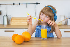 Portrait of a little girl in a blue dress drinks an orange juice and thinks Royalty Free Stock Photography