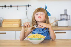 Portrait of a little girl in a blue dress funny eats a spaghetti Stock Photo