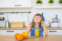 Portrait of a little girl in a blue dress funny eats a spaghetti Stock Images