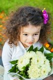 Portrait of little girl with bouquet of flowers. Portrait of little curly baby girl with bouquet of flowers close-up outdoors Stock Photography