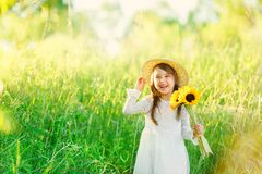 Portrait of little girl with a bouquet of wild yellow flowers standing and smiles in the meadow sunny summer day in a straw hat. royalty free stock image