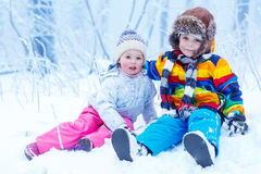 Portrait of little girl and boy in winter hat in snow forest at. Portrait of two kids: boy and girl in winter hat in snow forest at snowflakes background Royalty Free Stock Photography