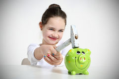 Portrait of little girl breaking piggy bank. Isolated on white Stock Photography