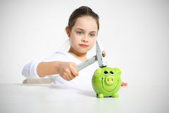 Portrait of little girl breaking piggy bank. Isolated on white Royalty Free Stock Images