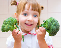 Portrait of a little girl with broccoli. Portrait of a happy little girl with broccoli in kitchen Stock Images