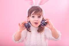 Portrait of a little girl with Bunny ears and Easter eggs. Portrait of a cute little girl with Bunny ears and Easter eggs, isolated on pink background stock photography