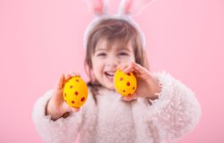 Portrait of a little girl with Bunny ears w Easter eggs. Portrait of a cute little girl with Bunny ears and yellow Easter eggs in red polka dots isolated on pink royalty free stock photo