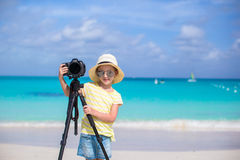 Portrait of little girl with camera on a tripod at white sandy beach Stock Images