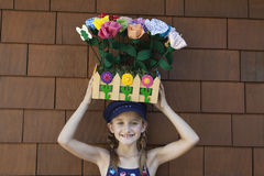 Portrait of little girl carrying artificial flowers in wooden crate on head Stock Photography