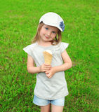 Portrait of little girl child in cap with ice cream on the grass Royalty Free Stock Images