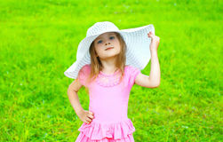 Portrait of little girl child in dress and straw hat in summer Stock Photo