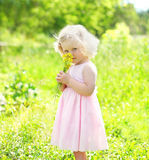 Portrait little girl child with flowers in spring. Field Royalty Free Stock Images