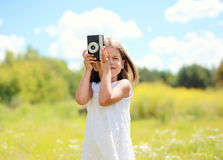 Portrait of little girl child with retro vintage camera outdoors Stock Image