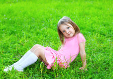 Portrait of little girl child sitting on the grass Stock Photo