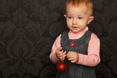 Portrait of little girl with Christmas toy in hand Royalty Free Stock Photography