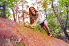 Side view of girl climbing on the rock in forest royalty free stock photos