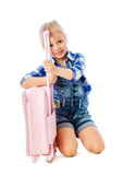 Portrait of a little girl collects suitcase vacation rental Stock Image
