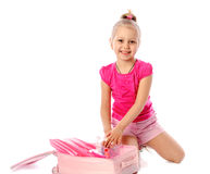 Portrait of a little girl collects suitcase vacation rental Stock Photos
