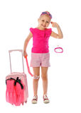 Portrait of a little girl collects suitcase vacation rental Royalty Free Stock Photo