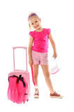 Portrait of a little girl collects suitcase vacation rental Royalty Free Stock Photos