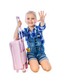 Portrait of a little girl collects suitcase vacation rental Royalty Free Stock Image