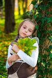 Portrait  little girl with colored maple leaves . Stock Photos