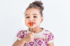 Portrait of a little girl in a colorful dress with a lollipop on a white background stock images