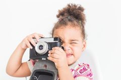 Portrait of a little girl in a colorful dress taking pictures on an old vintage camera royalty free stock photography