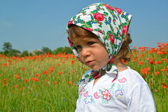 Portrait of the little girl in a colorful kerchief against red poppies Stock Images