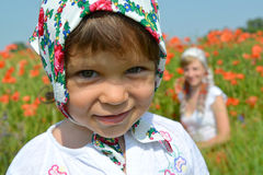 Portrait of the little girl in a colorful kerchief against red ppoppies Royalty Free Stock Images
