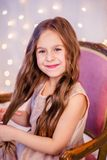 Portrait of a little girl with curly hair on Christmas Eve, the New Year will bring gifts. Cheerful emotions in anticipation of a surprise stock photography