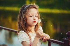 Little girl with dandelion in park Stock Photo