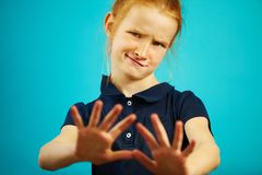Portrait of little girl with dissatisfied expression of denial pulls her hands into the camera, showing repulsion or royalty free stock photos
