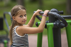 Portrait of little girl doing warm-up on the Playground. Sport. Royalty Free Stock Images