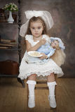 Little Caucasian girl is feeding her doll Royalty Free Stock Image