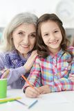 Portrait of little girl drawing with her grandmother stock photos
