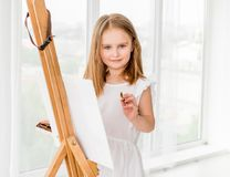 Portrait of a little girl drawing a picture on easel Royalty Free Stock Photo