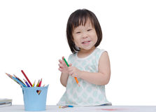 Portrait of a little girl drawing a sketch. Portrait of a little Asian girl drawing a sketch over white royalty free stock photos