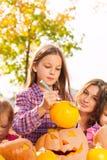 Portrait of little girl draws on Halloween pumpkin Royalty Free Stock Image