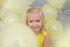 Portrait of a little girl in a dress with balloons. Portrait of a pretty little girl in a yellow dress with a yellow balloons Stock Photos