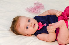 Portrait of a little girl in a dress in a diaper, which lies on the bed in her room. Portrait of a baby girl in a dress with diapers with a bow on her head which Royalty Free Stock Photos