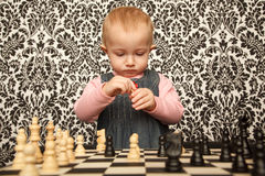 Portrait of little girl in dress playing chess Stock Photo