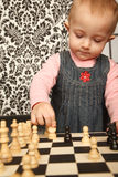 Portrait of little girl in dress playing chess Stock Image