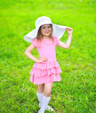 Portrait of little girl in dress and straw hat on the grass Royalty Free Stock Photography