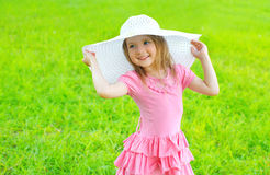 Portrait of little girl in dress and straw hat in summer Stock Images
