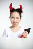 Portrait of little girl dressed as pretty imp. Showing a tongue Royalty Free Stock Photography