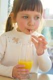 Portrait of  little girl drinking juice. Portrait of a cute little girl drinking orange juice Stock Images