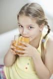 Portrait of little girl drinking orange juice Royalty Free Stock Photo