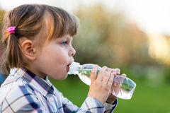 Portrait of little girl drinking water outdoor Stock Image